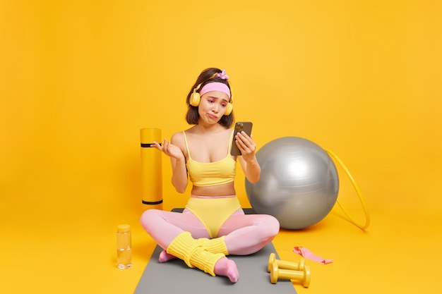 Woman looks with clueless expression at smartphone display takes break after aerobics or fitness training leads healthy lifestyle dressed in sportswear poses on mat in full length