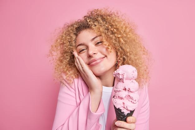 여자는 카메라를 즐겁게 보고 뺨에 손을 대고 미소를 짓고 세련된 재킷을 입은 와플에 맛있는 큰 아이스크림을 부드럽게 들고 있습니다