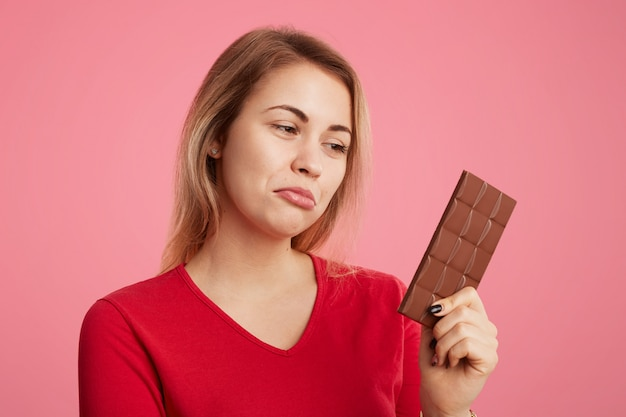Woman looks with discontent expression at sweet bar of chocolate, keeps to diet, can't eat it to be slim and sporty