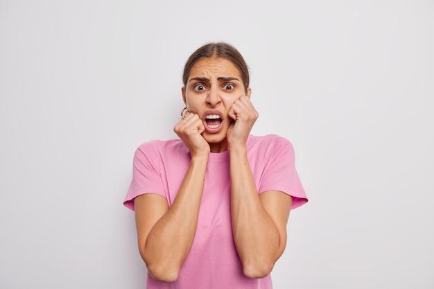 La donna guarda con un'espressione spaventata e inorridita reagisce a qualcosa di sgradevole vestita con una maglietta rosa casual su bianco