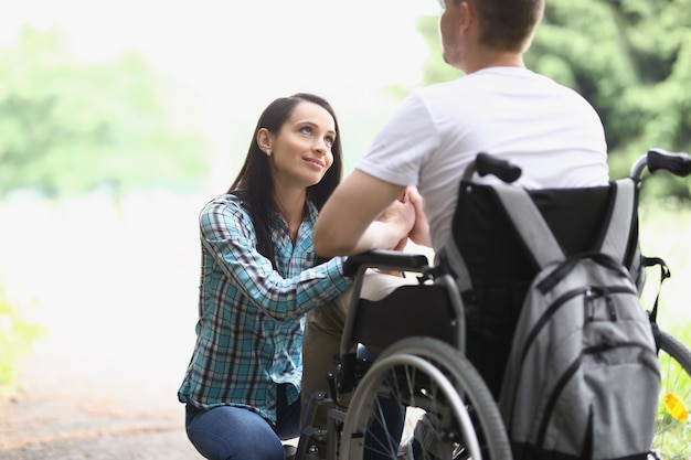 Woman looks with loving gaze at man in wheelchair