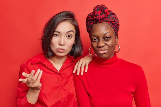 여자는 여자 친구 근처에서 분개하는 어리둥절한 몸짓으로 보인다. 불만족한 아프리카계 미국인 모델은 나쁜 소식을 좋아하지 않아 생생한 빨간색으로 얼굴을 찌푸립니다.