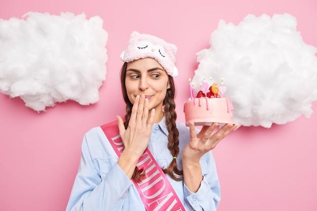 Женщина с искушением смотрит на вкусный торт против, рот ждет гостей на день рождения, носит рубашку с маской для сна, изолированную на розовом