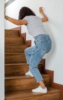 Женщина теряет контроль и не может ходить по лестнице, она останавливается и использует стену для удержания рук для поддержки с чувством и покалыванием. концепция синдрома гийена-барре и эффекта болезни онемевших рук.