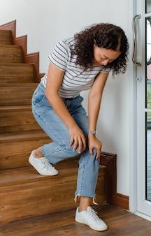 Женщина теряет контроль и не может ходить по лестнице, она останавливается и держится за колени для поддержки и отдыха, чувствуя покалывание. понятие синдрома гийена-барре и болезни онемения ног или побочного эффекта вакцины.