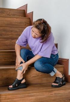 Женщина теряет контроль и не может ходить по лестнице, она останавливается и держится за ноги для поддержки и отдыха, чувствуя покалывание. понятие синдрома гийена-барре и болезни онемения ног или побочного эффекта вакцины.
