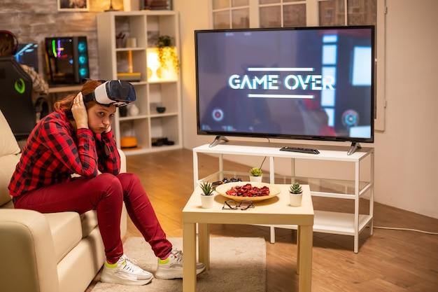 Женщина проигрывает в видеоиграх, играя с гарнитурой виртуальной реальности поздно ночью в гостиной