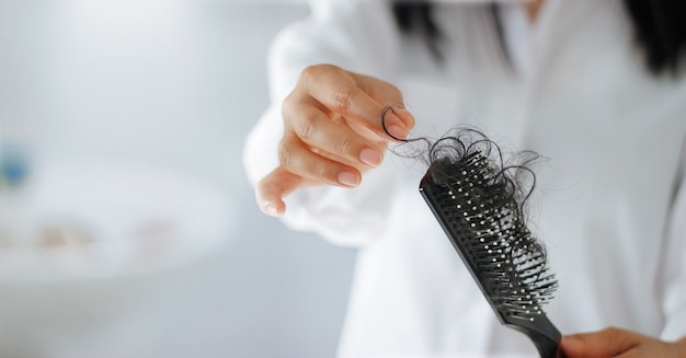 Woman losing hair on hairbrush in hand
