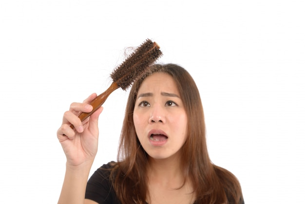 Woman losing hair on hairbrush isolated on white
