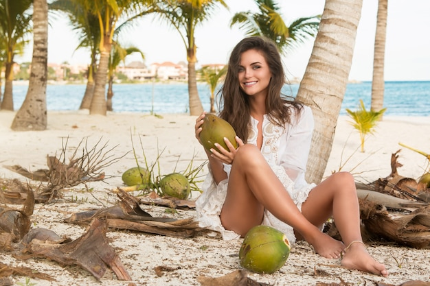 Woman and lot of coconuts on the ground