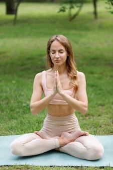 Woman in lotus pose namaste yoga in summer park