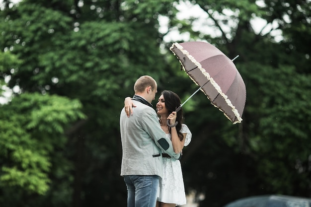 Woman in love with umbrella looking at her boyfriend
