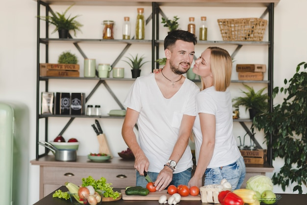 Woman loving her boyfriend cutting red tomato with knife in kitchen