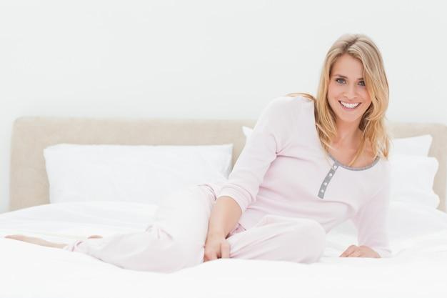 침대의 길이에 걸쳐 누워있는 여자, 한쪽 무릎이 접혀 웃고