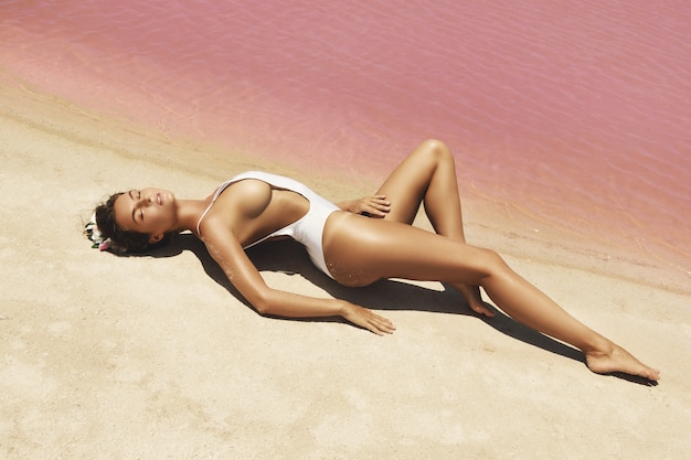 Woman lying on the beach with pink water