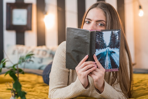 Woman lying on bed covering her mouth with book