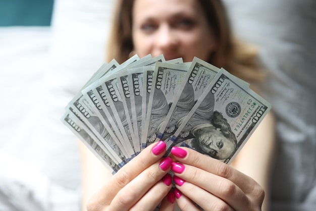 Woman lying in bed and holding many dollars in her hands closeup