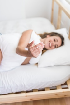 Woman lying on bed inviting someone