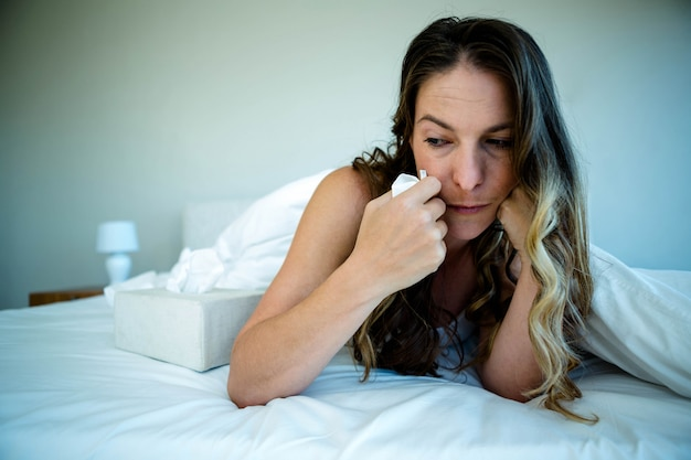 Woman lying in bed looking upset and holding a tissue in her hand