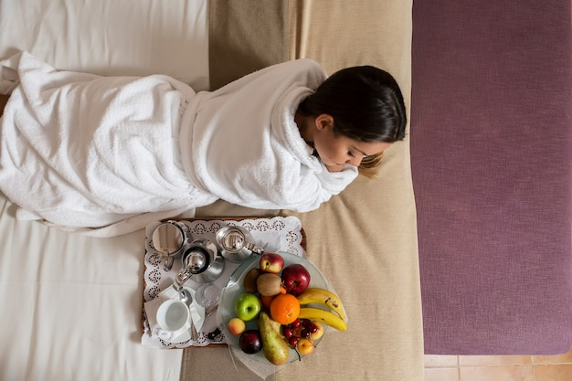 Woman lying on bed near plate of fruits