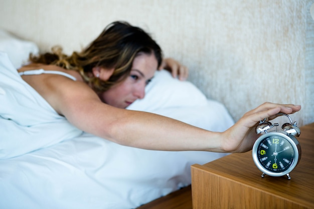 Woman lying in bed, reaching out to turn off her alarm clock