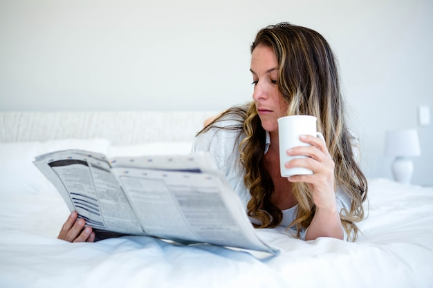 Woman lying in bed reading the newspaper and drinking