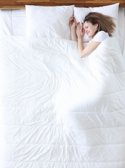 Woman lying in bed and smiling top view. comfortable bedding concept