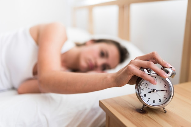 Woman lying on bed turning off alarm clock in bedroom