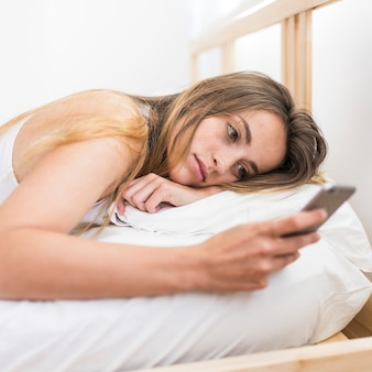 Woman lying on bed using mobile phone
