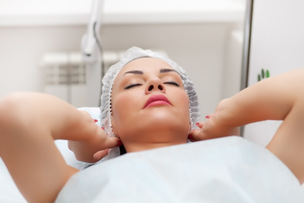 Woman lying on bed while getting beauty injection in neck. facial treatments. beauty concept.