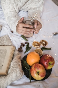 Woman lying on bed with cocktail and fruits