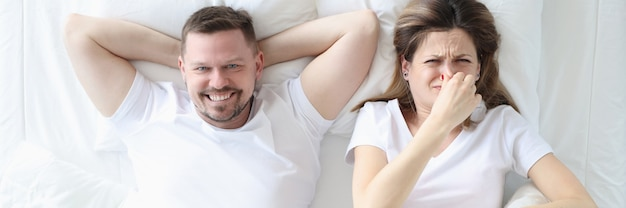 Woman lying in bed with man and covering her nose with her hand increased gas formation concept