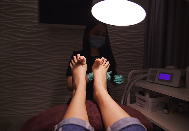 Woman lying on a chair and enjoying professional pedicure in beauty salon.