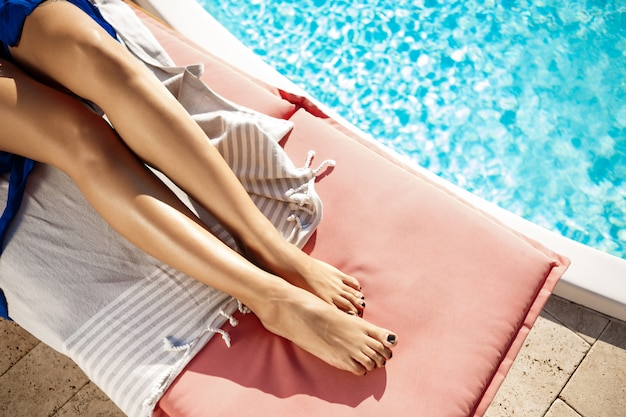 Woman lying on chaise near swimming pool