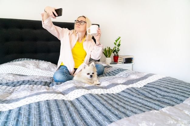 Woman lying in a cozy bed with her dog and reading a book