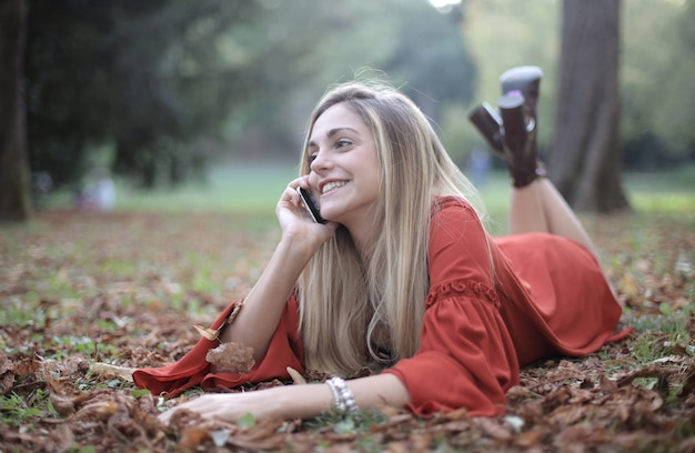 Woman lying down on the forest floor and talking on the phone