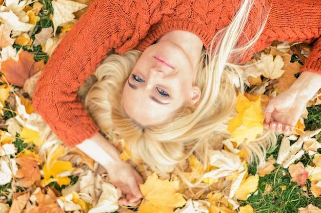 Женщина, лежа на желтых листьях