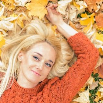 黄色の葉の上に横たわっている女性