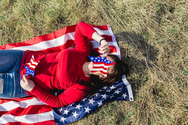 Woman lying on fabric of american flag on field