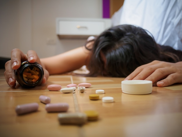 Woman lying on the floor with a lot of pills. overdose and suicide concept.