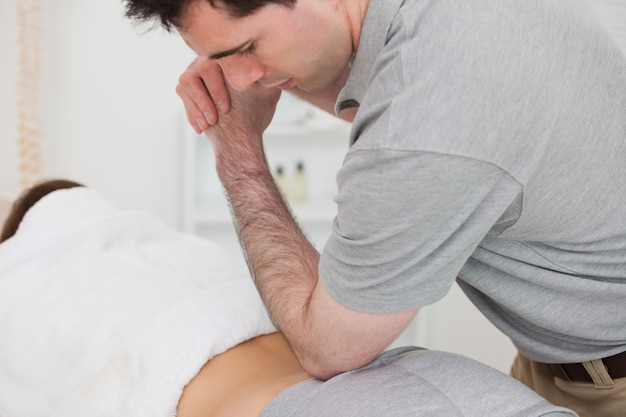 Woman lying forward while a physiotherapist is massaging her back