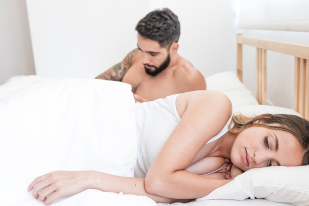 Woman lying in front of her husband on bed