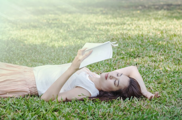 Woman lying on grass field for reading in the park