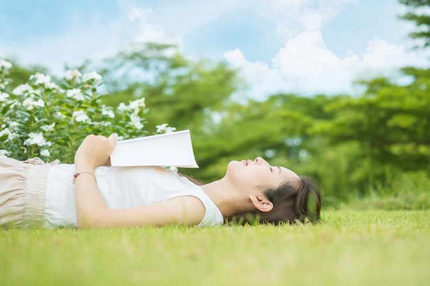A woman lying grass field for sleeping after she tired for reading a book