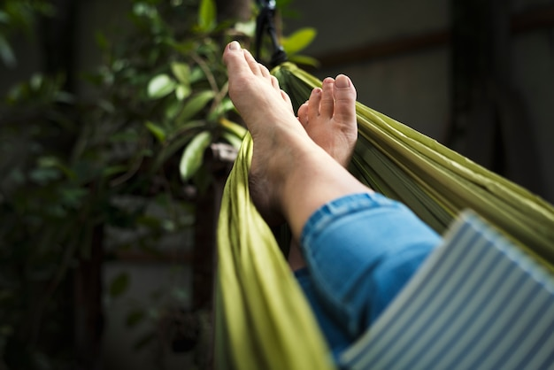 Woman lying on hammock chilling reading book
