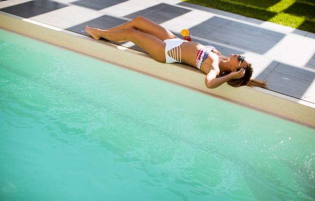 Woman lying on her back on pool edge sunbathing in her bikini