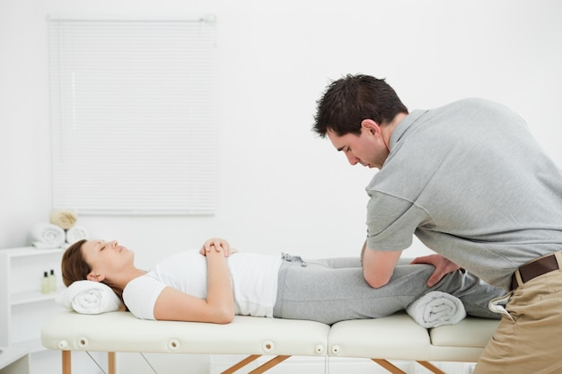 Woman lying on her back while being massaged by a man