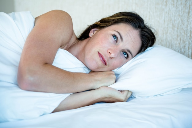 Woman lying in her bed looking amused