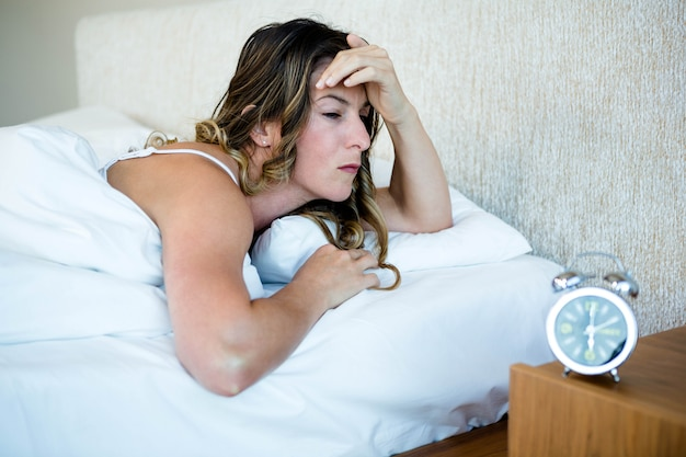 Woman lying in her bed looking stressed, next to an alarm clock