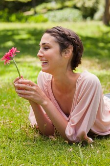 Woman lying on her front laughing while looking at a flower